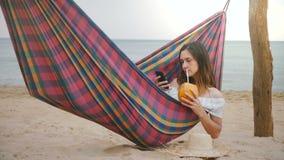 Ευτυχής επιτυχής νέα επιχειρηματίας στην αιώρα παραλιών στην παραλία με το κοκτέιλ φρούτων που χρησιμοποιεί το κινητό παιχνίδι ap φιλμ μικρού μήκους