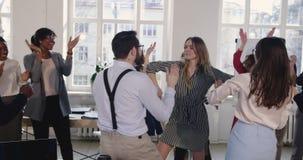 Ευτυχής επιτυχής ξανθή επιχειρησιακή γυναίκα που κάνει τον περίπατο χορού εορτασμού διασκέδασης με τους συναδέλφους στο σύγχρονο  απόθεμα βίντεο