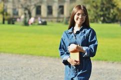 Ευτυχής επιτυχής όμορφη γυναίκα που διασχίζει τα χέρια και που χαμογελά κοντά στην πανεπιστημιούπολη στοκ εικόνα με δικαίωμα ελεύθερης χρήσης