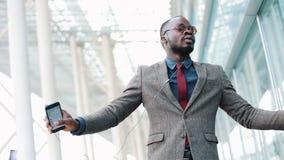 Ευτυχής επιχειρηματίας αφροαμερικάνων που ακούει τη μουσική στα ακουστικά στο smartphone, περπατώντας έξω από το γραφείο και αστε απόθεμα βίντεο