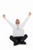Ευτυχής επιχειρηματίας ενθαρρυντικός και συνεδρίαση με το lap-top του Στοκ Εικόνες