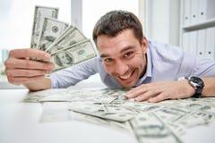 Ευτυχής επιχειρηματίας με το σωρό των χρημάτων στην αρχή Στοκ Φωτογραφία