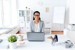 Ευτυχής επιχειρηματίας με το lap-top που λειτουργεί στο γραφείο Στοκ φωτογραφία με δικαίωμα ελεύθερης χρήσης