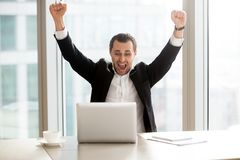 Ευτυχής επιχειρηματίας μπροστά από το lap-top που γιορτάζει το εντυπωσιακό achi Στοκ Εικόνες