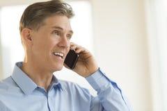 Ευτυχής επιχειρηματίας που απαντά στο έξυπνο τηλέφωνο Στοκ Εικόνα