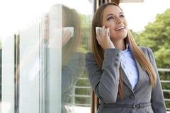 Ευτυχής επιχειρηματίας που απαντά στο τηλέφωνο κυττάρων από την πόρτα γυαλιού Στοκ Εικόνες