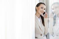 Ευτυχής επιχειρηματίας που απαντά στο τηλέφωνο κυττάρων στην αρχή Στοκ φωτογραφίες με δικαίωμα ελεύθερης χρήσης