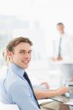 Ευτυχής επιχειρηματίας που εξετάζει τη κάμερα κατά τη διάρκεια μιας συνεδρίασης Στοκ Εικόνες