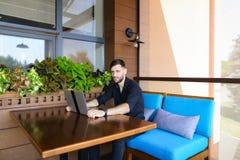 Ευτυχής επιχειρηματίας που εξετάζει τη κάμερα που λειτουργεί με το lap-top και τη συζήτηση Στοκ Εικόνες