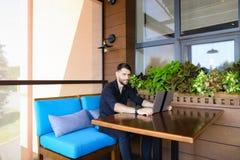 Ευτυχής επιχειρηματίας που εξετάζει τη κάμερα που λειτουργεί με το lap-top και τη συζήτηση Στοκ Φωτογραφίες