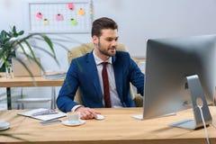 ευτυχής επιχειρηματίας που εξετάζει τον υπολογιστή Στοκ Εικόνες