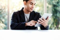 Ευτυχής επιχειρηματίας που εργάζεται στην ψηφιακή ταμπλέτα στην αρχή Κάθισμα στο γραφείο και χαμόγελο στοκ φωτογραφία