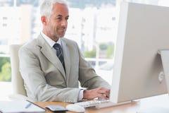 Ευτυχής επιχειρηματίας που εργάζεται στον υπολογιστή Στοκ Εικόνες