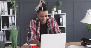 Ευτυχής επιχειρηματίας που εργάζεται στο lap-top στο γραφείο απόθεμα βίντεο