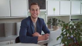 Ευτυχής επιχειρηματίας που εργάζεται στο lap-top στο σύγχρονο γραφείο απόθεμα βίντεο
