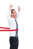 Ευτυχής επιχειρηματίας που διασχίζει τη γραμμή τερματισμού και που δείχνει επάνω Στοκ εικόνες με δικαίωμα ελεύθερης χρήσης