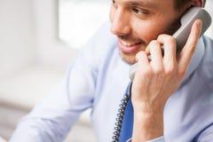 Ευτυχής επιχειρηματίας που καλεί το τηλέφωνο στο γραφείο Στοκ Εικόνα