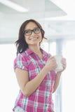Ευτυχής επιχειρηματίας που κοιτάζει μακριά κρατώντας την κούπα καφέ στο δημιουργικό γραφείο Στοκ Εικόνες