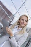 Ευτυχής επιχειρηματίας που κοιτάζει μακριά κρατώντας την ψηφιακή ταμπλέτα ενάντια στο κτίριο γραφείων Στοκ Εικόνες