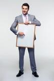 Ευτυχής επιχειρηματίας που κρατά τον κενό πίνακα Στοκ εικόνες με δικαίωμα ελεύθερης χρήσης