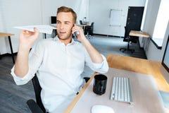 Ευτυχής επιχειρηματίας που μιλά στο κινητό τηλέφωνο και που ρίχνει το αεροπλάνο εγγράφου Στοκ Εικόνες