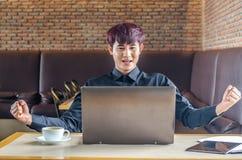 Ευτυχής επιχειρηματίας που ο στόχος του και που παρουσιάζει πυγμές με το lap-top Στοκ εικόνες με δικαίωμα ελεύθερης χρήσης