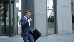 Ευτυχής επιχειρηματίας που παρουσιάζει χειρονομία επιτυχίας, που αφήνει το κτίριο γραφείων, επίτευγμα απόθεμα βίντεο