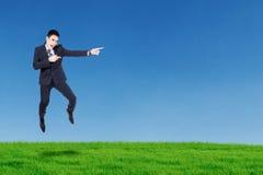 Ευτυχής επιχειρηματίας που πηδά και που δείχνει κάτι Στοκ Φωτογραφία