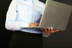 Ευτυχής επιχειρηματίας που στέκεται με το lap-top που απομονώνεται σε ένα μαύρο υπόβαθρο Στοκ Εικόνες