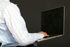 Ευτυχής επιχειρηματίας που στέκεται με το lap-top που απομονώνεται σε ένα μαύρο υπόβαθρο Στοκ εικόνες με δικαίωμα ελεύθερης χρήσης