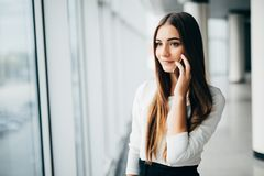 Ευτυχής επιχειρηματίας που στέκεται στο γραφείο της σε ένα πολυόροφο κτίριο που χτίζει αγνοώντας τη εικονική παράσταση πόλης κινη Στοκ φωτογραφία με δικαίωμα ελεύθερης χρήσης