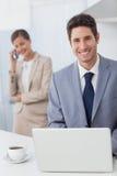 Ευτυχής επιχειρηματίας που χρησιμοποιεί ένα lap-top πρίν πηγαίνει να εργαστεί Στοκ Εικόνες