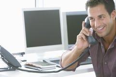 Ευτυχής επιχειρηματίας που χρησιμοποιεί το τηλέφωνο γραμμών εδάφους στην αρχή Στοκ Εικόνες