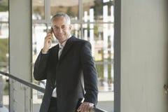 Ευτυχής επιχειρηματίας που χρησιμοποιεί το τηλέφωνο κυττάρων Στοκ Φωτογραφία