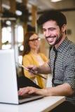 Ευτυχής επιχειρηματίας που χρησιμοποιεί το lap-top με το θηλυκό συνάδελφο Στοκ Φωτογραφίες