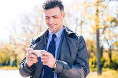 Ευτυχής επιχειρηματίας που χρησιμοποιεί το smartphone Στοκ Εικόνες