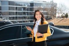 Ευτυχής επιχειρηματίας ρ που στέκεται κοντά στο αυτοκίνητο και που χρησιμοποιεί το κινητό τηλέφωνο στοκ φωτογραφία