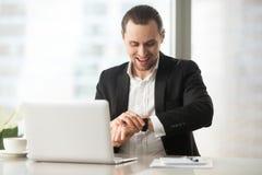 Ευτυχής επιχειρηματίας στην εργασία που εξετάζει το wristwatch με το μεγάλο χαμόγελο Στοκ Φωτογραφίες