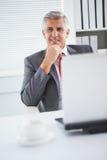 Ευτυχής επιχειρηματίας στο γραφείο του Στοκ Φωτογραφία