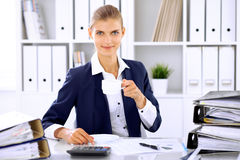 Ευτυχής επιχειρησιακή γυναίκα ή θηλυκός λογιστής που έχει μερικά πρακτικά για τον καφέ και την ευχαρίστηση στη θέση εργασίας στοκ εικόνα