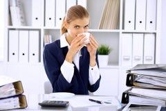 Ευτυχής επιχειρησιακή γυναίκα ή θηλυκός λογιστής που έχει μερικά πρακτικά για τον καφέ και την ευχαρίστηση στη θέση εργασίας Στοκ εικόνα με δικαίωμα ελεύθερης χρήσης