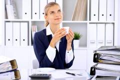 Ευτυχής επιχειρησιακή γυναίκα ή θηλυκός λογιστής που έχει μερικά πρακτικά για τον καφέ και την ευχαρίστηση στη θέση εργασίας Στοκ φωτογραφία με δικαίωμα ελεύθερης χρήσης