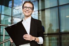 Ευτυχής επιχειρησιακή γυναίκα, επιτυχές πορτρέτο επιχειρησιακής κυρίας, έγγραφα εκμετάλλευσης διευθυντών Στοκ Εικόνες
