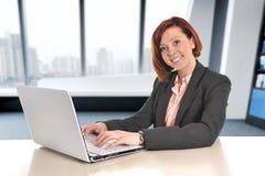 Ευτυχής επιχειρησιακή γυναίκα με την κόκκινη τρίχα που χαμογελά στη δακτυλογράφηση εργασίας στο lap-top υπολογιστών στο σύγχρονο  Στοκ Φωτογραφίες