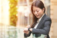 Ευτυχής επιχειρησιακή γυναίκα που εξετάζει το smartwatch της Στοκ Φωτογραφία