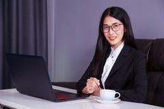 Ευτυχής επιχειρησιακή γυναίκα που εργάζεται στο φορητό προσωπικό υπολογιστή και το εναλλασσόμενο ρεύμα κατανάλωσης Στοκ Φωτογραφία