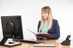 Ευτυχής επιχειρησιακή γυναίκα που κρατά ένα βιβλίο στα χέρια του γραφείου και που εξετάζει τον υπολογιστή Στοκ φωτογραφία με δικαίωμα ελεύθερης χρήσης