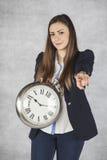 Ευτυχής επιχειρησιακή γυναίκα που κρατά ένα ρολόι και που δείχνει σε σας Στοκ Εικόνες