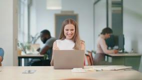 Ευτυχής επιχειρησιακή γυναίκα που λαμβάνει τις καλές ειδήσεις στο lap-top στην αρχή Γυναίκα freelancer απόθεμα βίντεο