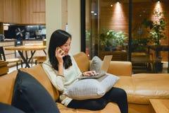 Ευτυχής επιχειρησιακή γυναίκα που μιλά στο τηλέφωνο στο καθιστικό κοντά στοκ φωτογραφίες